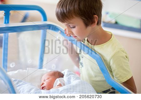 Beautiful newborn baby boy laying in crib in prenatal hospital his brothers looking at him with adore
