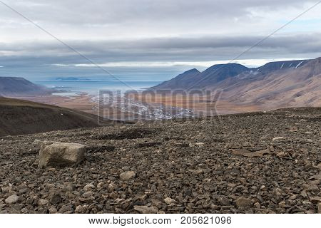 Loose rocks on Breinosa mountainin in Svalbard Norway. Scenic view of arctic landscape Adventdalen (Advent valley) Adventfjorden (Advent fjord) and Longyerbyen in background