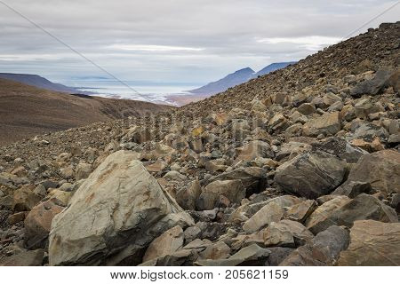 Loose rocks on Breinosa mountainin in Svalbard Norway. Scenic view of arctic landscape Adventdalen (Advent valley) and Adventfjorden (Advent fjord) and Longyerbyen in background