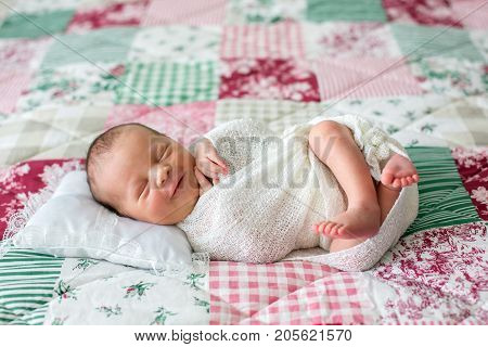 Beautiful Newborn Baby Boy, Widely Smiling, Wrapped In Wrap, Lying Down In Bed