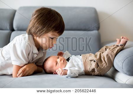 Sweet Preschool Boy, Hugging With Tenderness And Care His Little Newborn Brother