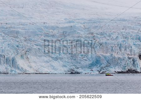 Unidentified tourists on a speedboat admiring large Nordenskiold glacier (Nordenskioldbreen) from a close distance in Svalbard Norway