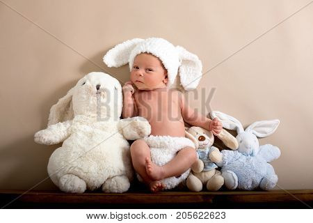Newborn Baby Boy Wearing A Brown Knitted Rabbit Hat And Pants, Sleeping On A Shelf