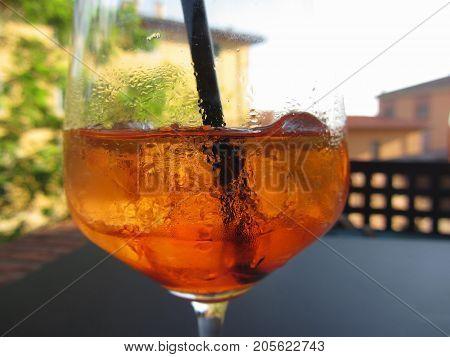 Summer refreshing aperitif drink on the rocks . Spritz cocktail with lemon slice