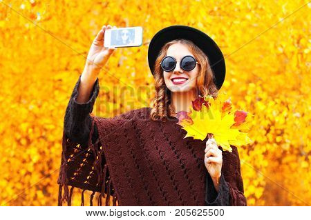 Autumn Fashion Smiling Young Woman Taking A Picture Self Portrait On The Smartphone, Wearing A Knitt