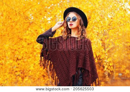 Autumn Fashion Woman Wearing A Black Round Hat, Knitted Poncho On A Yellow Leaves Background