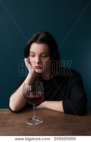 Lonely female in bar. Melancholic mood. Sad woman with red wine on blue background with free space, unsuccessful romantic date. Problems in life, sadness concept