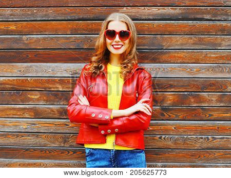 Fashion Autumn Smiling Woman Wearing A Red Leather Jacket On A Wooden Background