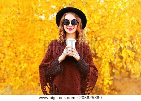 Fashion Autumn Woman Holds Coffee Cup In Black Round Hat, Knitted Poncho On A Yellow Leaves Backgrou
