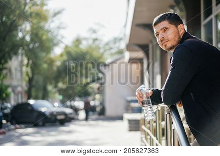 Portrait of a young man standing in the street holding a bottle of mineral water. Enjoying drinking water.