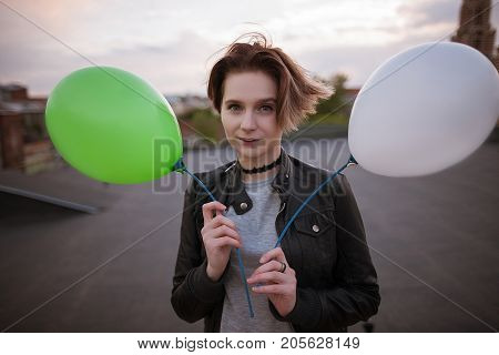 Enigmatic young woman with two toy balloons, close up. Party and celebration, walk around the city, hope and infantile personality concept