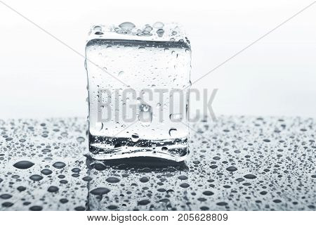 Transparent ice cube with reflection on white background. Closeup of cold crystal block on glass with water drops