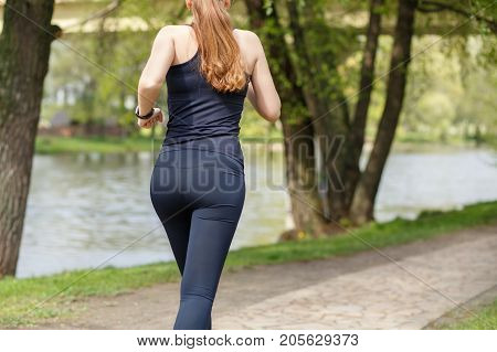 Young sporty woman running in park. Fitness girl jogging in park. Rear view of sporty girl running on embankment