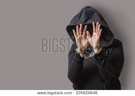 a girl in a black hood with handcuffed hands hides her face. isolated on a gray background.