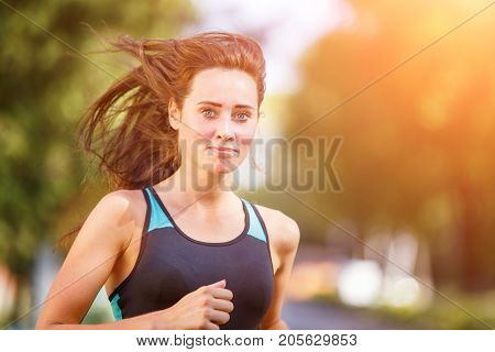 Portrait of young smiling sporty woman running in park in the morning. Fitness girl jogger portrait with copyspace
