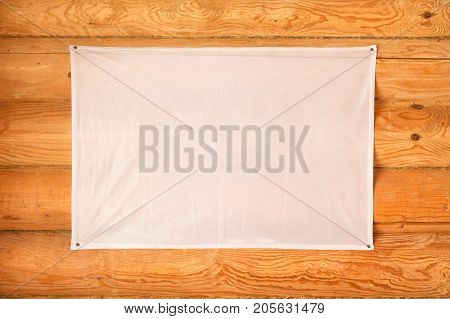 A blank flag of cloth hanging a wooden blockhouse wall made of cylindered logs. Mock up