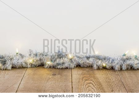 Tinsel With White Christmas Lights Along Edge Of Rustic Plank Surface, White Background