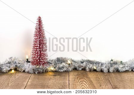 Red Sparkly Christmas Tree On Rustic Wooden Surface With Lights And Tinsel