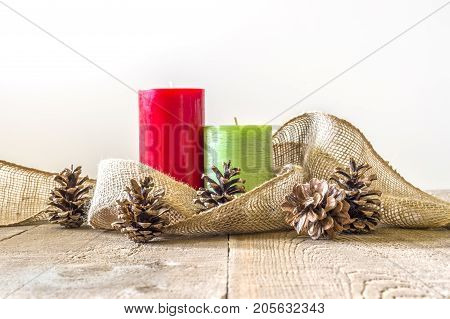 Red And Green Candles With Burlap Wrapped Around And Pinecones On Rustic Wood Table