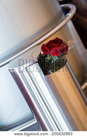 fake farewell, red roses in a trash of shiny metal at the airport