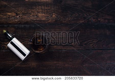 Bad habits advertising top view closeup. Alcoholic drink and vape on wooden background with free space, entertainment for rich people, after work relaxation, addiction concept