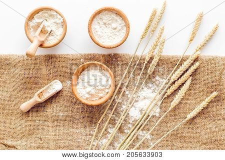 Production of wheat and rye flour from ear on white desk background in bakery top view