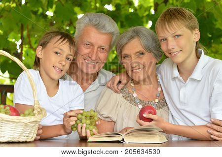Grandparents and grandsons sitting at wooden table with opened book and basket with fruits