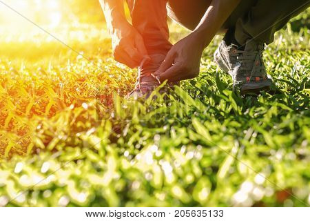 Sport exercise, Runner tie shoelaces in shoes. Healthy lifestyle Outdoor activity in sunset time.