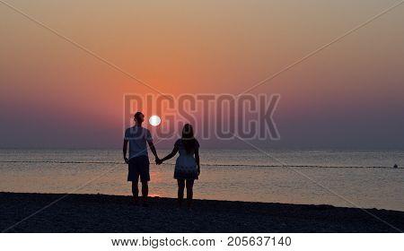 happy young couple is enjoying the sunrise