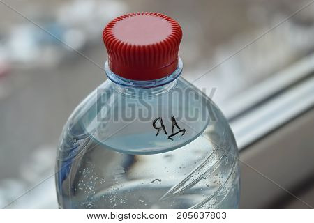 A one-and-a-half-liter bottle with poison and an inscription of poison on the Cyrillic alphabet stands on the windowsill near the window.
