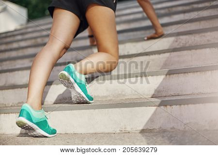 Close up of woman preparing to run upstairs or doing push ups. Urban sport concept.
