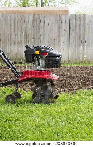 a tiller machine plowing a garden in spring.