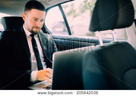 Handsome Businessman Sitting With Laptop On The Backseat Of The Car