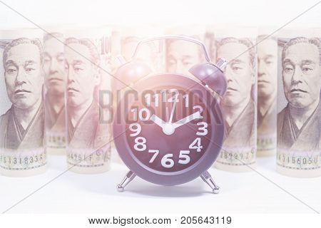 Classic Clock On Roll Of Yen Banknote Concept And Idea Of Time Value And Money Business And Finance Concepts Money market in Asia