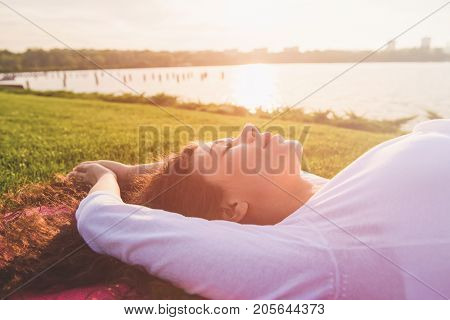 Beautiful young pregnant woman doing yoga on river bank. Woman lying on her back on a yoga mat. Female face closed eyes close-up. River setting sun in the background