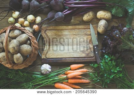 Fresh vegetables from carrot, beetroot, onion, garlic, potato on old wooden board. Top view. Autumn still life. Gardening. Copy space on cutting board. Matte.