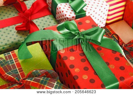 Gift wrapping background closeup. Packaging modern christmas present. Lots of gift boxes in stylish modern colored paper, decorated with red, green satin ribbon bows
