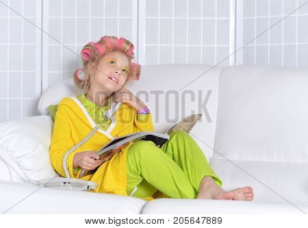 cute little girl reading magazine and talking on phone