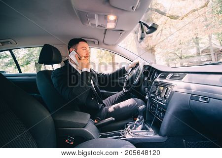 Man Using His Phone While Driving The Car. Business Man Driver Speak Phone White Drive Car
