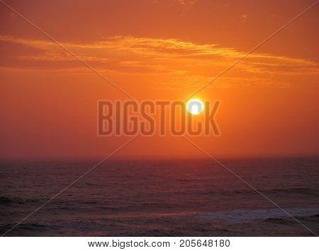 SUN SETTING UNDER A GOLDEN ORANGE SKY OVER THE HORIZON OF THE ATLANTIC OCEAN, NEAR CAPE TOWN, SOUTH AFRICA