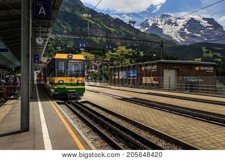 Wengen Bernese Oberland Switzerland - JULY 31 2017 : Train of the Wengernalpbahn from Lauterbrunnen to Kleine Scheidegg in railwaystation in car-free village Wengen. Jungfrau mountain in the background.