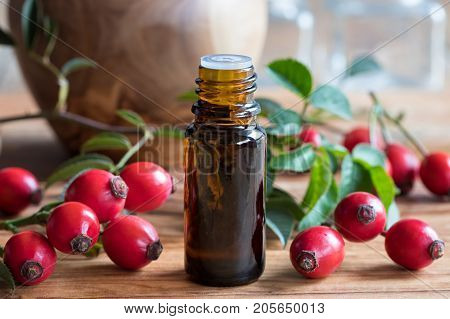 A Bottle Of Rosehip Seed Oil On A Wooden Table