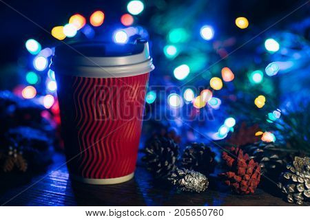 Delicious Christmas celebration with latte. Close up cup of warm energy drink and strobila decoration on defocused fairy lights background. Cozy xmas evening in cafe and fairs, happy holiday concept
