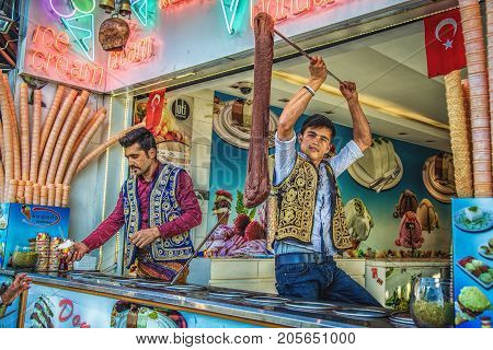ISTANBUL TURKEY: Young dondurma ice-cream sellers dressed in traditional Turkish costume in the street shop on May 2 2017