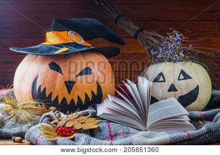 Halloween Concept: Pumpkins, Hat, Book And Autumn Leaves On A Wooden Background.