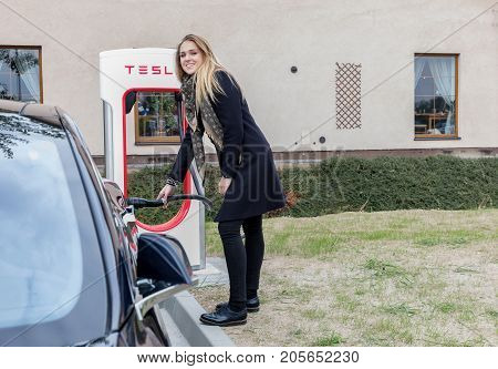 VESTEC CZECH REPUBLIC - SEPTEMBER 23 2017. Young woman joins a car to the Supercharger Tesla station. Supercharger charging station for electromobiles. Tesla cars park at the Tesla Supercharger.