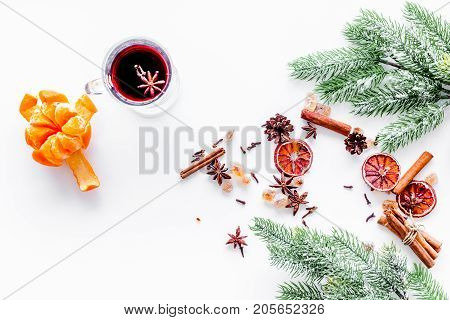 Hot mulled wine or grog cooking for new year celebration with oranges and spices ingredients on white table background flat lay mock up