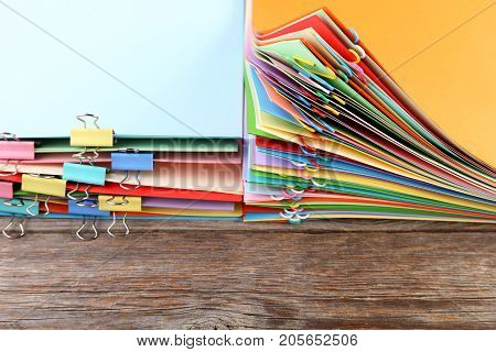 Stack Of Colored Papers With Paperclips And Clamps On Wooden Table