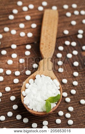Sweetener Tablets In Wooden Scoop With Mint Leaf On Wooden Table