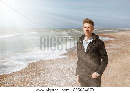 young man walking along the seashore in the sun rays